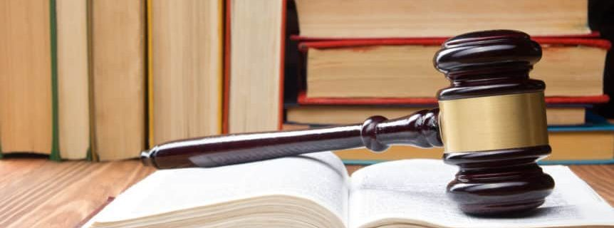 Law concept - Law book with a wooden judges gavel on table in a courtroom or law enforcement office